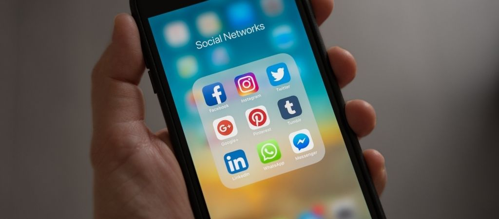 Image shows a close up of a hand holding a smartphone. The screen is on, with a group of social apps on display - These include Facebook, Instagram, Twitter, LinkedIn.
