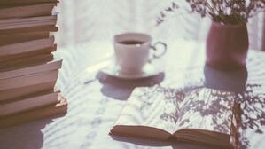 An open book and a cup of tea on a sunny windowsill