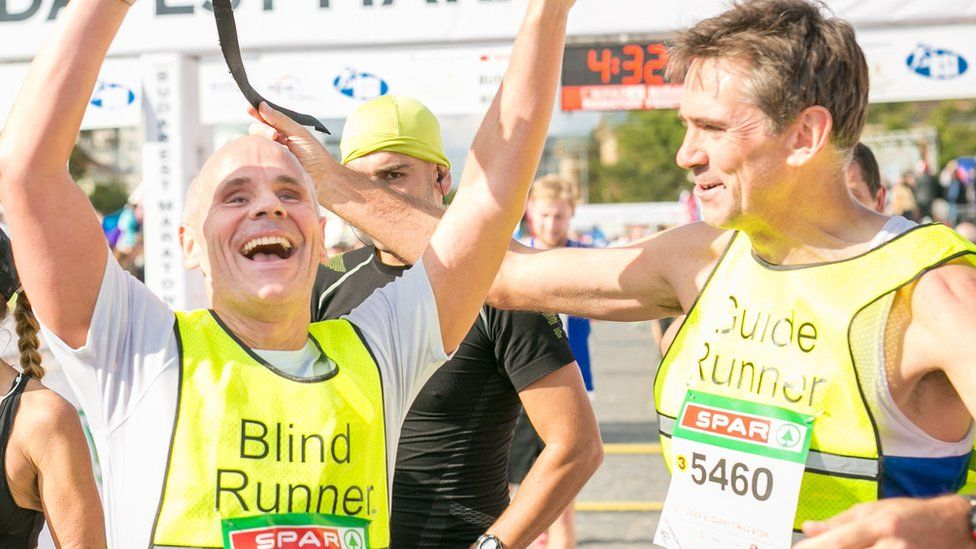 Chris Blackabee smiles and celebrates with his arms in the air at the end of a race, alongside Guide runner Colin Johnson. Both are wearing high vis vests and their race numbers the race finish line can be seen in the background