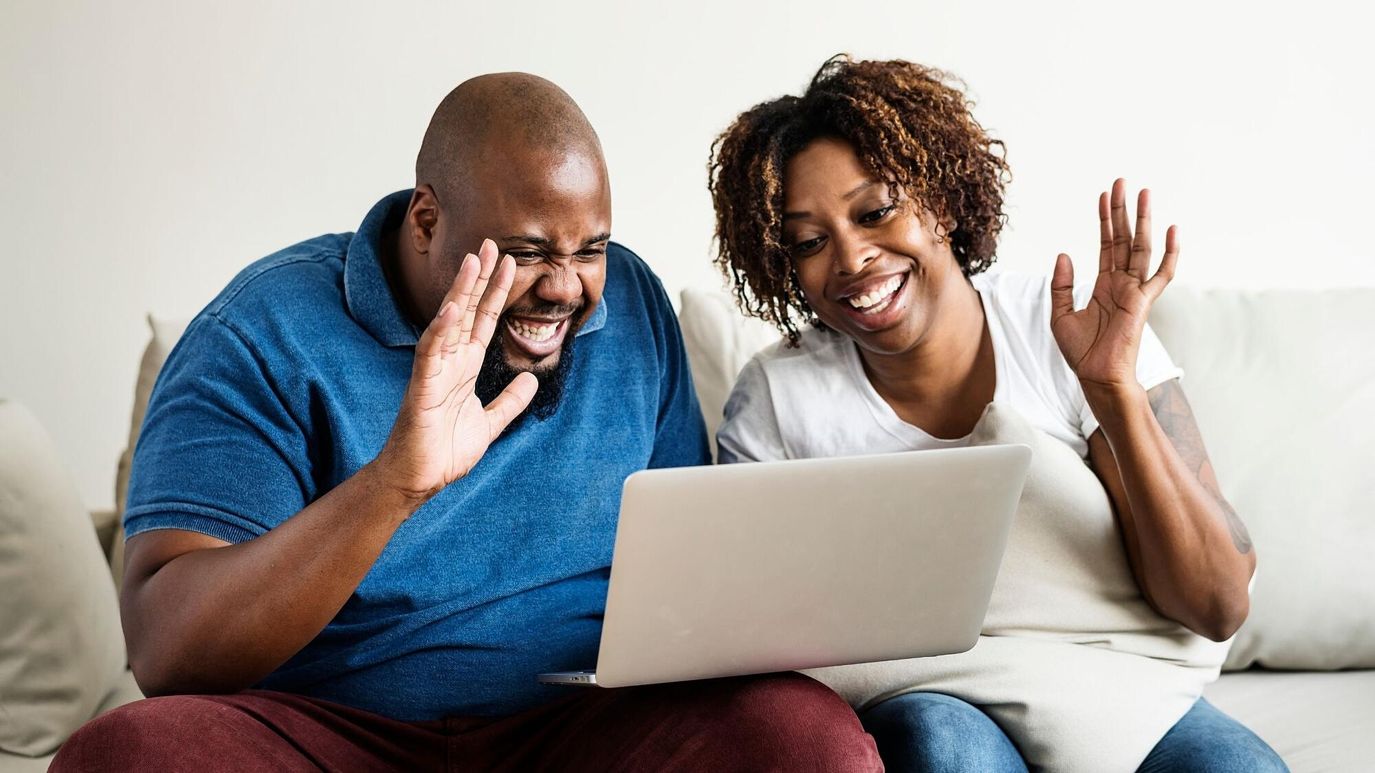 Couple waving towards screen on video call
