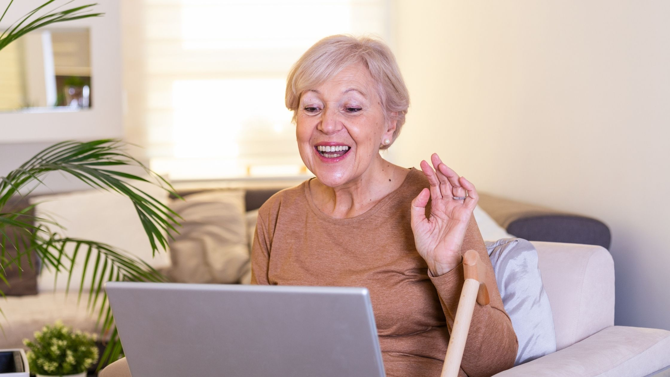 Lady on sofa waves happily towards laptop computer screen
