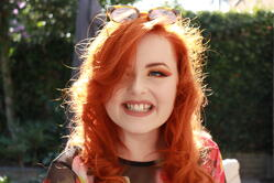 Image of Lucy Edwards. Lucy is smiling at the camera and is standing outside in the sunshine