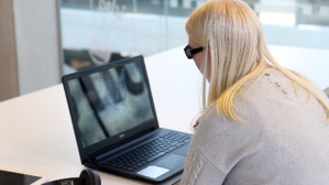 Student Charlotte is sitting at a desk with an open laptop in front of her.