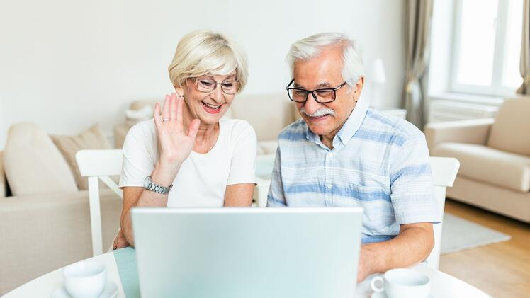 Older couple smile at laptop screen while on video call