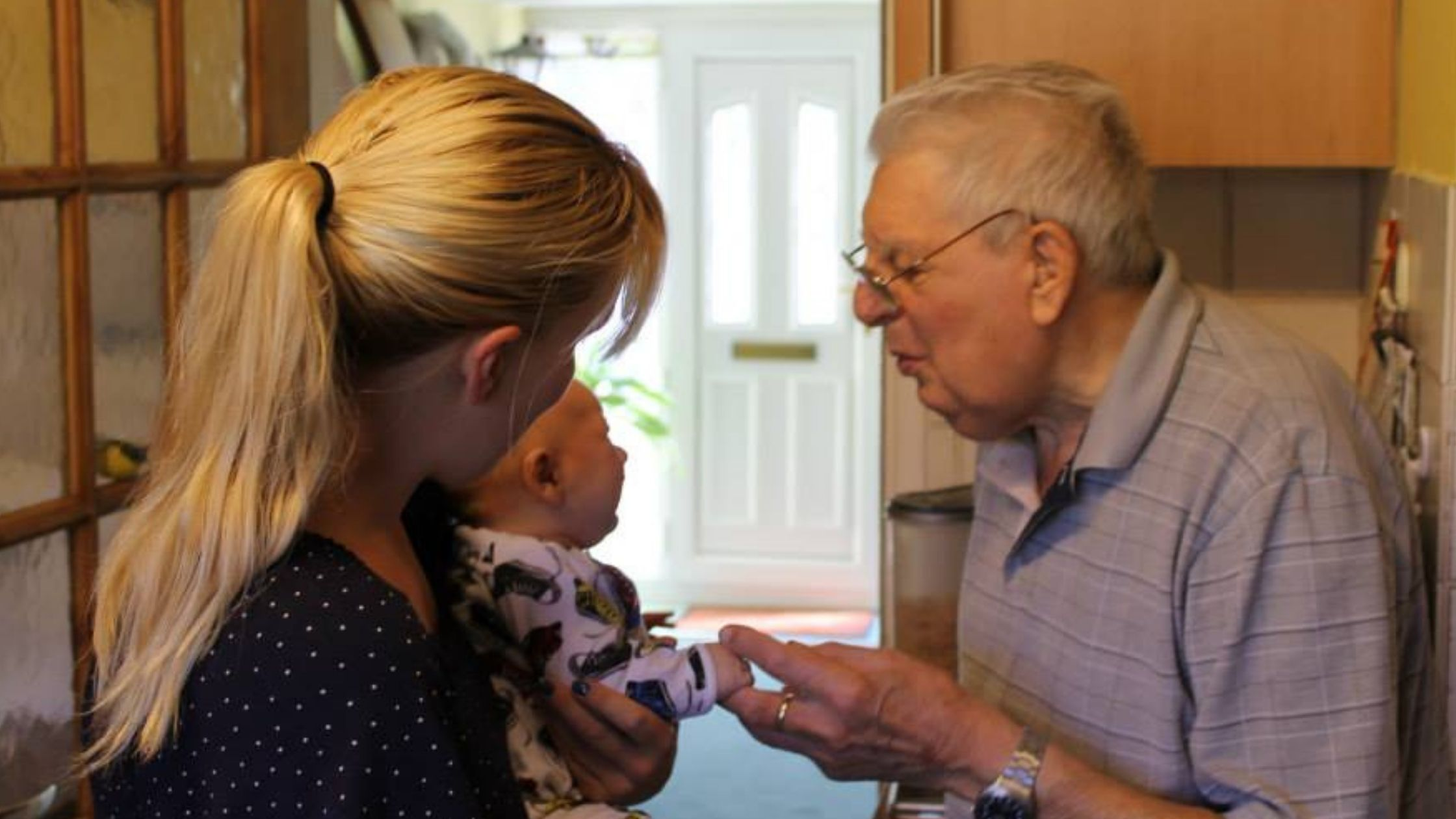 Image shows me holding my baby son and my grandad holding his hand and talking to him