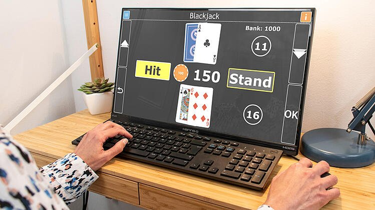 Image shows a desktop computer screen, with the hands of a person playing Blackjack on GuideConnect on the keyboard