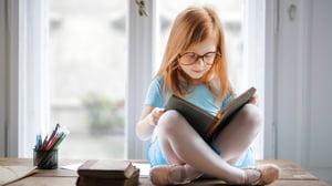 child sitting cross legged reading a book