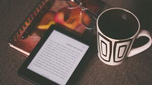 ebook and notebook next to a cup of coffee