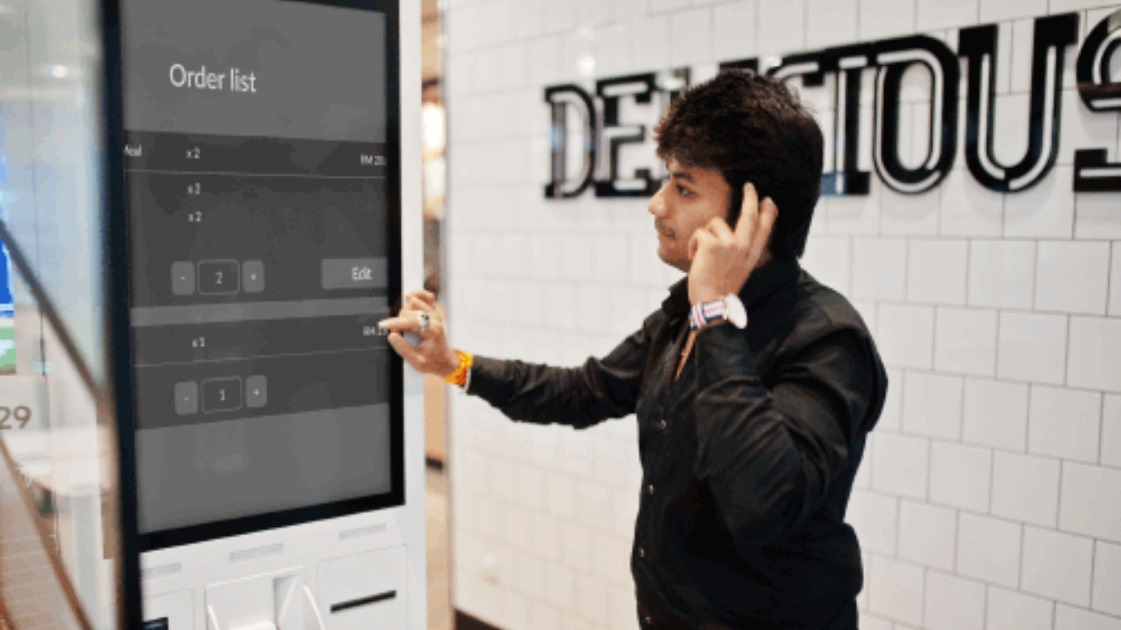 Image shows man using a self service kiosk screen to adjust an order. The screen has an enhanced display with large text and options