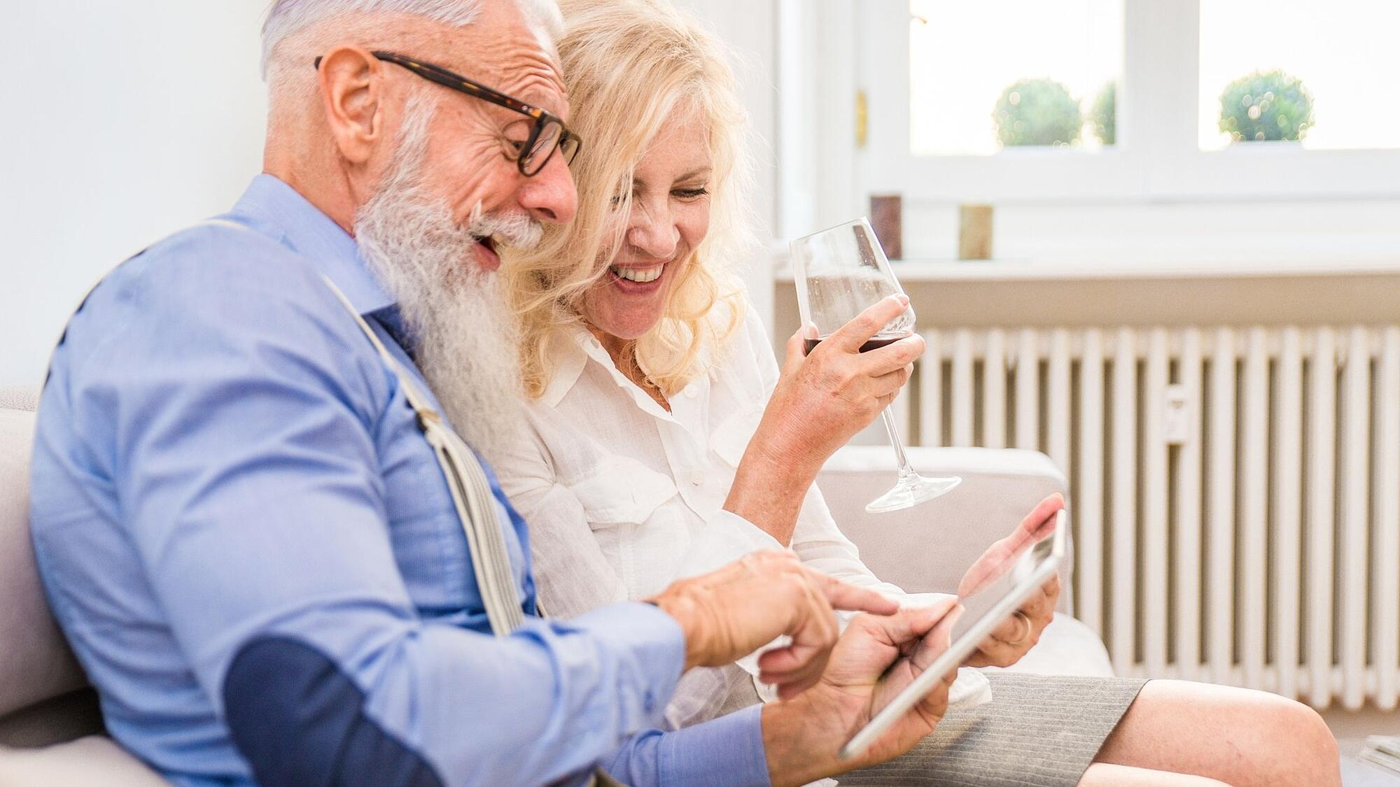 laughing couple looking at screen on computer tablet