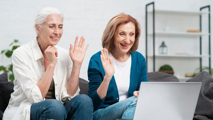 two friends wave and smile toward open laptop on video call