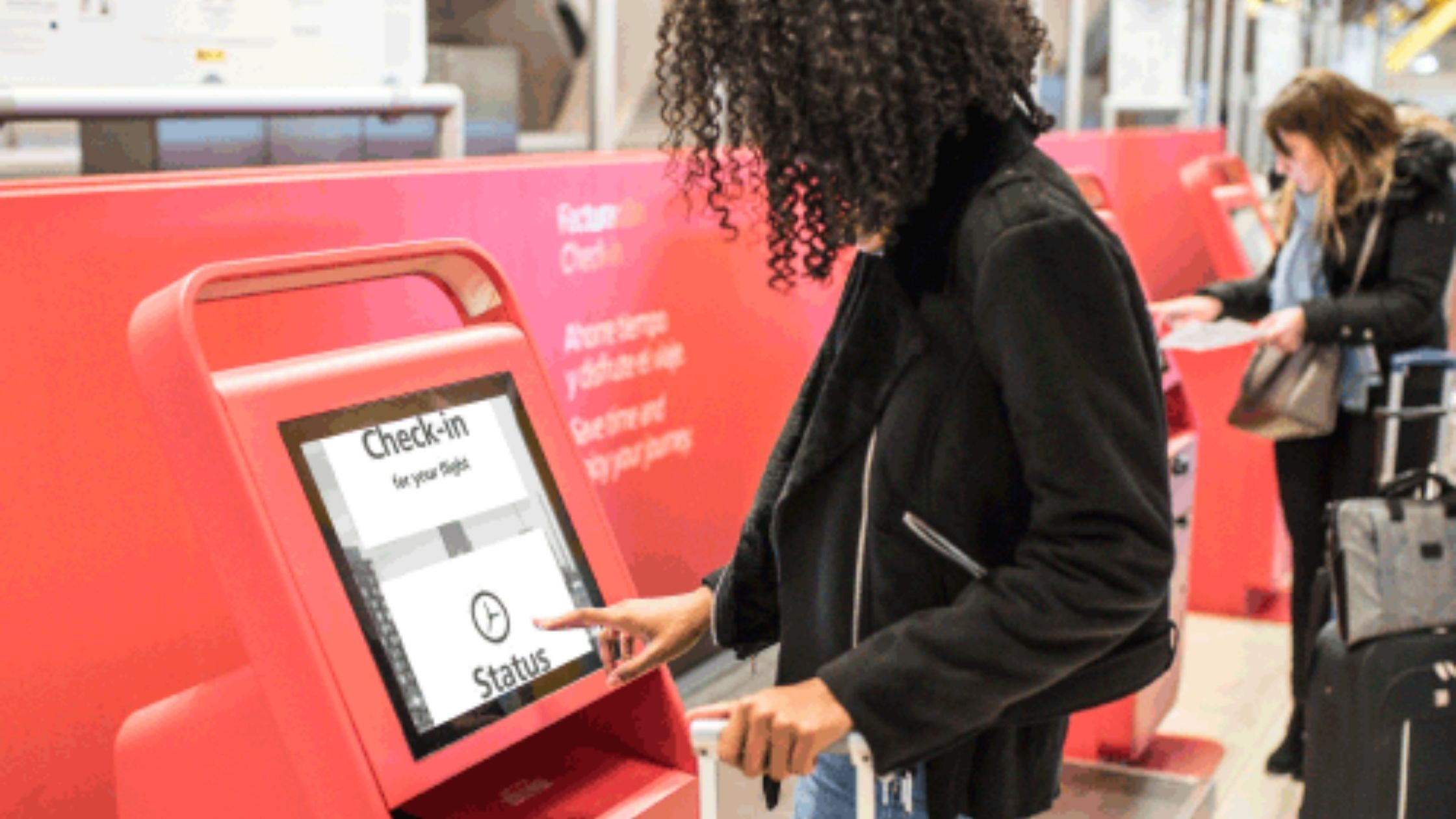 Image shows person using a self service kiosk screen to check in at an airport.  The screen has an enhanced display with large text.